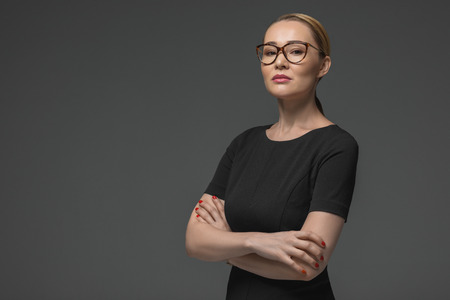 portrait of beautiful kazakh woman in eyeglasses looking at camera isolated on grey