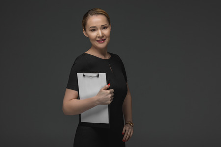 beautiful kazakh businesswoman holding clipboard and smiling at camera isolated on grey Stok Fotoğraf