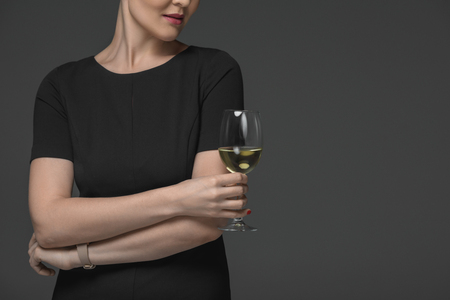 cropped shot of woman in black dress holding glass of white wine isolated on grey Stok Fotoğraf - 112769692