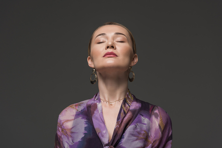 portrait of sensual kazakh woman with closed eyes isolated on grey