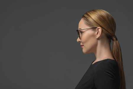 profile portrait of beautiful kazakh woman in eyeglasses looking away isolated on grey