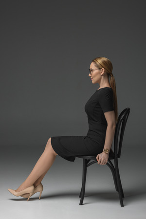 side view of beautiful kazakh woman in eyeglasses sitting on chair and looking away on grey Stok Fotoğraf