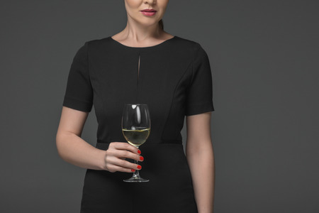 cropped shot of elegant woman holding glass of wine isolated on grey