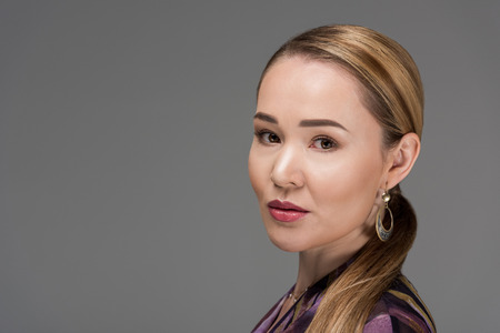 close-up portrait of beautiful elegant kazakh woman looking at camera isolated on grey