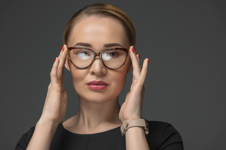portrait of beautiful kazakh woman wearing eyeglasses and looking at camera isolated on grey