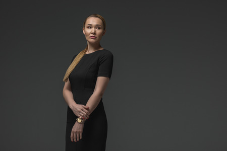 portrait of elegant kazakh woman in black dress posing isolated on grey