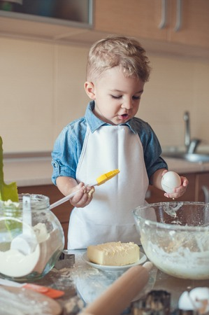 adorable boy holding egg and cooking brush and looking down Stock Photo - 112769764