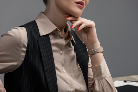 cropped shot of elegant kazakh businesswoman with hand on chin on grey Stok Fotoğraf