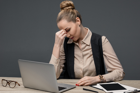 tired kazakh businesswoman using laptop at table isolated on grey Stok Fotoğraf