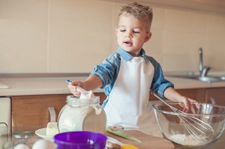 adorable boy taking flour with measuring cup Standard-Bild - 112769816