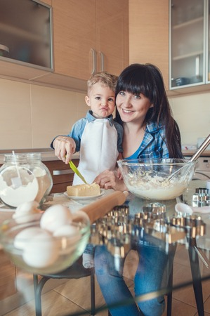 smiling mother helping son cut butter with plastic knife Archivio Fotografico