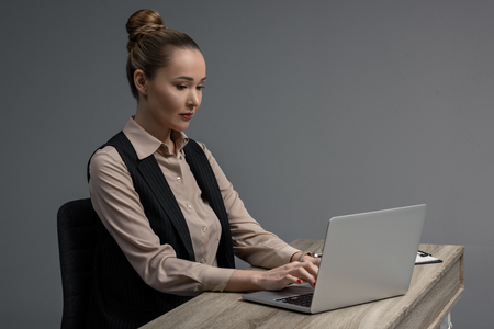beautiful kazakh businesswoman using laptop at table isolated on grey Stok Fotoğraf