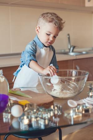 adorable boy adding flour to glass bowl Standard-Bild - 112769937