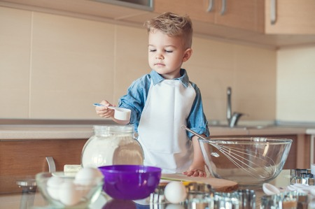 adorable boy taking flour with measuring cup