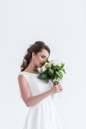 attractive bride with closed eyes sniffing wedding bouquet, isolated on white Imagens