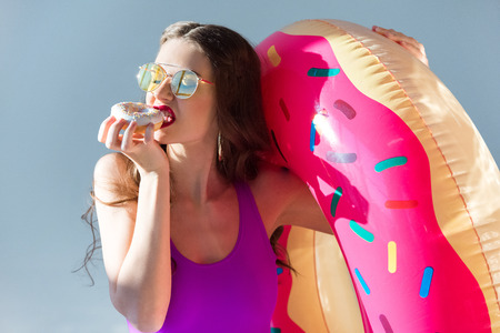 sexy attractive girl in ultra violet swimsuit eating doughnut isolated on grey