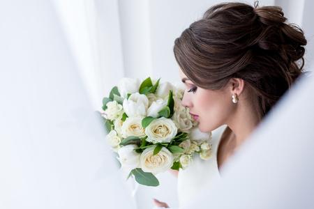 jolie mariée brune reniflant le bouquet de mariage