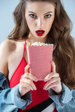 surprised sexy girl holding popcorn and looking at camera Stok Fotoğraf