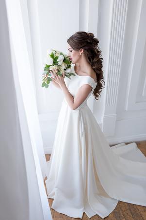 elegant bride in traditional white dress sniffing wedding bouquet Banco de Imagens