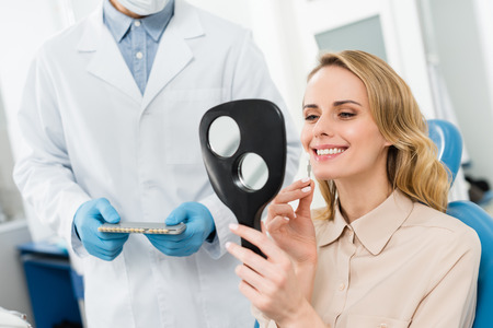 Woman choosing tooth implant looking at mirror in modern dental clinic