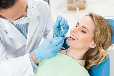 Doctor treats patient teeth in modern dental clinic