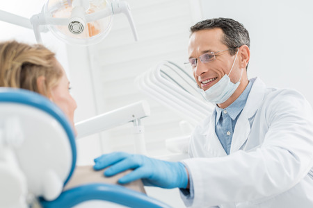Smiling doctor consulting female patient in modern dental clinic Stock Photo