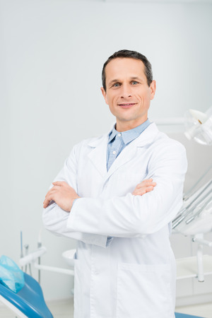 Confident doctor with folded arms in modern dental clinic Stock Photo