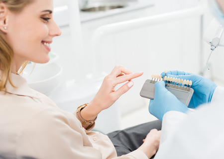 Doctor showing tooth implants to female patient in modern dental clinic Stockfoto