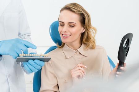 Dokter die tandimplantaten toont aan vrouwelijke patiënt in moderne tandheelkundige kliniek Stockfoto