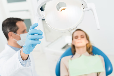 Doctor adjusting lamp in modern dental clinic