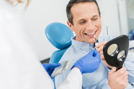 Male patient choosing tooth implant looking at mirror in modern dental clinic