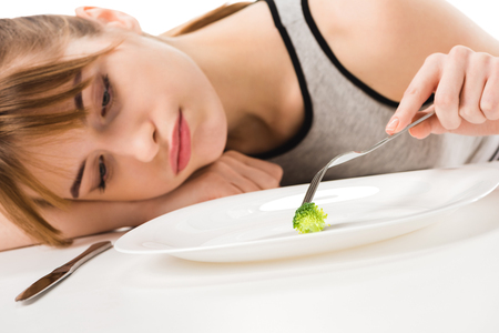 depressed slim woman eating piece of broccoli from plate isolated on white