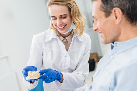 Doctor and patient looking at jaws model in modern dental clinic Banco de Imagens