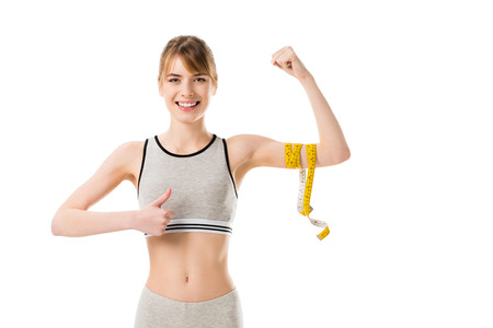 young slim woman showing her biceps tied with measuring tape and thumb up isolated on white 免版税图像