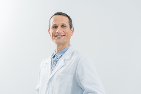 Smiling confident doctor by the wall in modern clinic Stock Photo