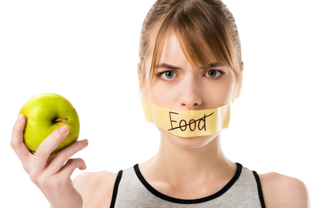 Young woman with stick tape with striked through word food covering mouth holding apple isolated on white
