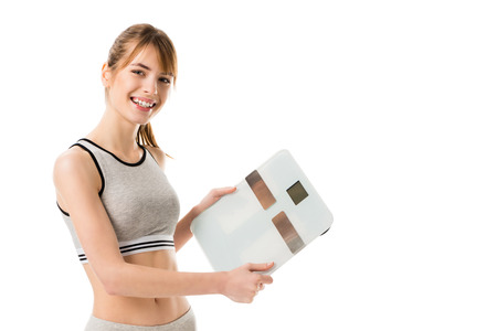 Happy slim woman holding scales isolated on white