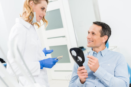 Male patient choosing tooth implant in modern dental clinic Stock Photo