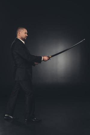Side view of mature man in suit with katana sword on dark background 写真素材