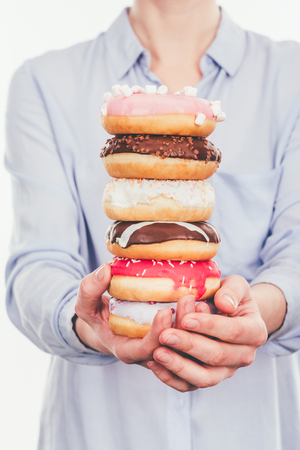 Cropped shot of woman holding stack of doughnuts isolated on white