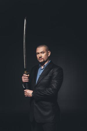 Modern samurai in formal suit with katana sword looking at camera on black