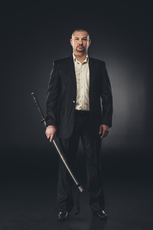 Mature handsome man in suit with katana on black 写真素材
