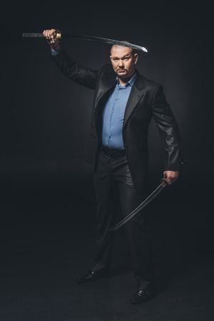 Man in suit with dual katana swords looking at camera on black