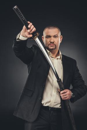 Man in suit taking of his katana sword on black