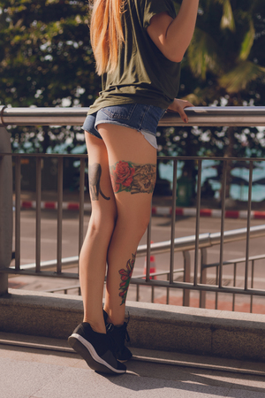 Cropped shot of tattooed young woman in shorts outdoors