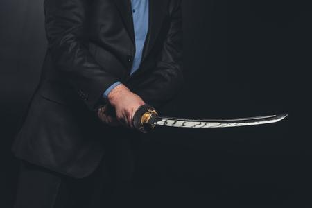 Cropped shot of man in suit holding Japanese katana sword on black 写真素材