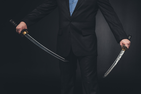 Cropped shot of man in suit with dual katana swords on black Stock Photo