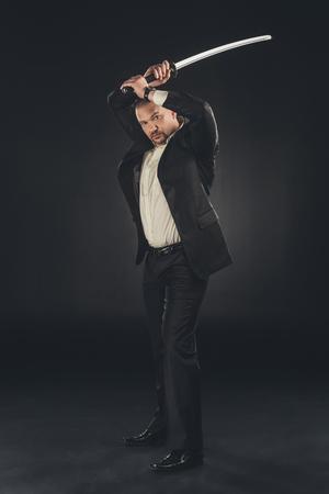 Yakuza member in suit with katana sword on black Stock Photo