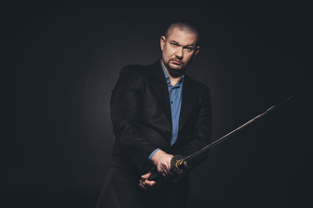 Serious man in suit with katana on black