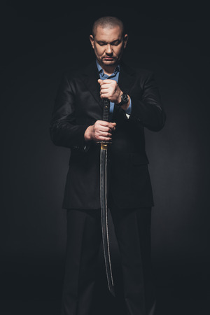 Man in suit with Japanese katana sword on black